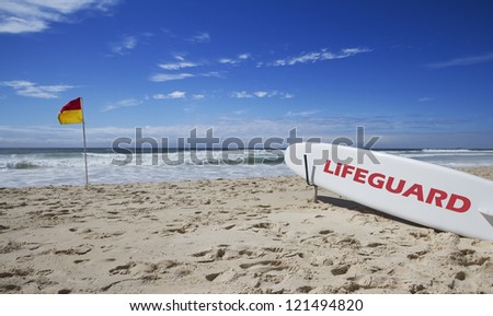Lifeguard surfboard on the beach near a safe swimming flag - stock photo