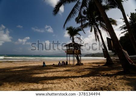 Lifeguard tower amid palms on tropical beach - stock photo