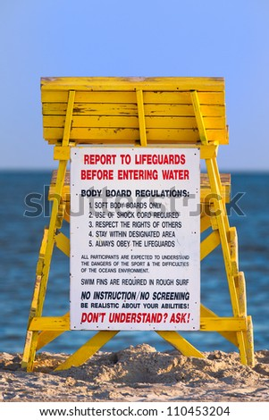 Lifeguard tower at a beach with regulations sign. - stock photo