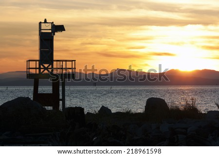 Lifeguard tower facing an orange sunset - stock photo
