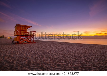 Lifeguard tower in a typical colorful Art Deco style at sunshine, with purple sky and Atlantic Ocean in the background. World famous travel location. Miami beach, Florida.