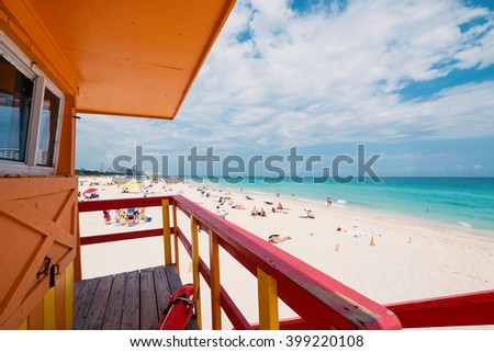 Lifeguard tower in a typical colorful Art Deco style on a bright sunny summer day, with blue sky and Atlantic Ocean in the background. World famous travel location. Miami beach, Florida. - stock photo
