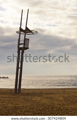 Lifeguard tower in the morning in an empty beach. Maintenance truck traces in the sand and cloudy sky. - stock photo