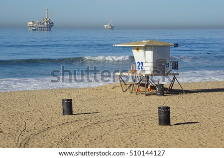 lifeguard tower on beach with oil platforms in background