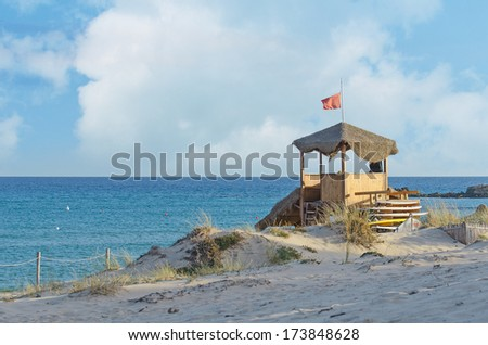 Lifeguard tower with red flag near the beach. - stock photo
