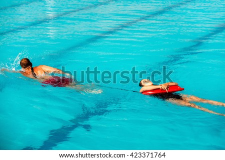 Lifeguard training - lifeguard pulling victim to safety, using floating rescue buoy