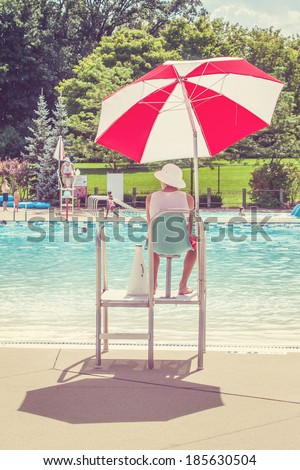 LIfeguard watching a swimming pool - stock photo