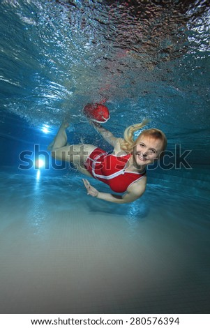 Lifeguard with red swimsuit and safety buoy swimming underwater in the pool