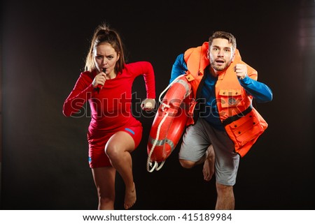 Lifeguards with rescue ring buoy lifebuoy and life vest jacket running to accident. Man and woman supervising swimming pool whistling on black. - stock photo