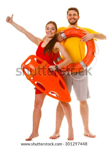 Lifeguards with rescue tube and ring buoy lifebuoy showing thumb up gesture. Man and woman supervising swimming pool. Accident prevention. - stock photo