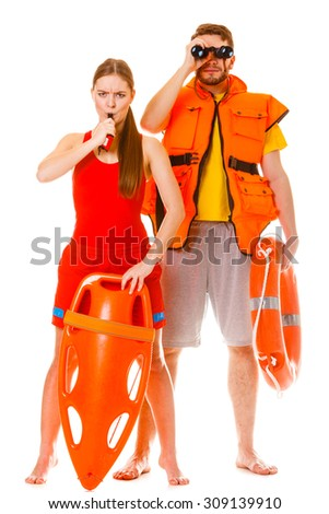 Lifeguards with rescue tube ring buoy lifebuoy and life vest jacket looking through binoculars. Man and woman supervising swimming pool whistling. Accident prevention. - stock photo