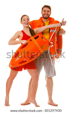 Lifeguards with rescue tube ring buoy lifebuoy and life vest jacket showing thumb up gesture. Man and woman supervising swimming pool. Accident prevention. - stock photo