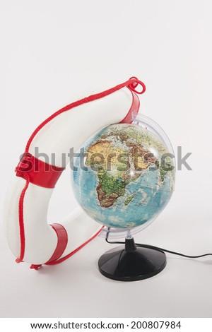 Lifesaver and globe against white background - stock photo