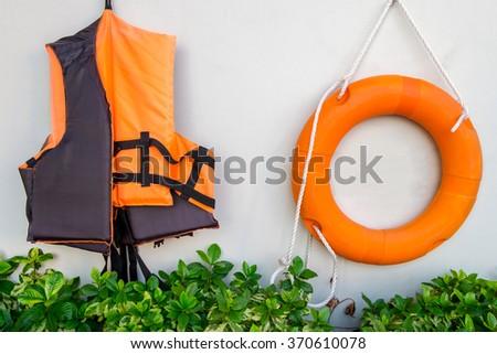 lifesaving jacket, Llife jacket ,life buoys lifesaving hang on wall. lifesaving ready to use. - stock photo