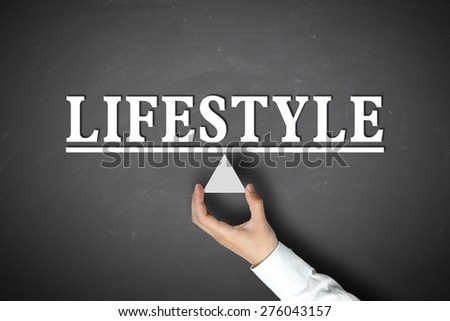 Lifestyle balance concept with businessman hand holding against blackboard background.