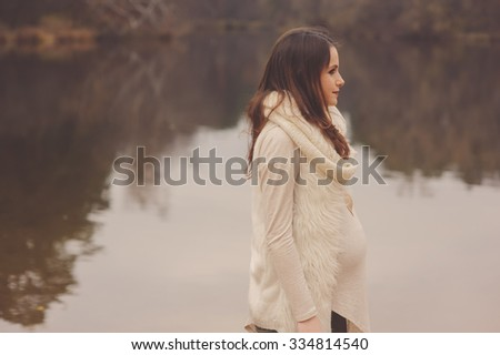 lifestyle capture of beautiful pregnant woman walks outdoor, soft warm toned, cozy mood, soft focus - stock photo