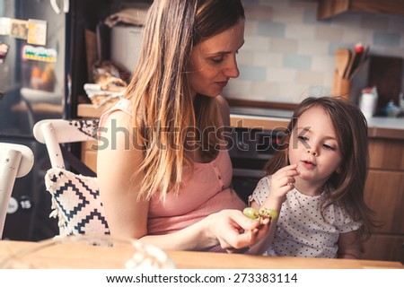lifestyle capture of pregnant woman with daughter on the kitchen having breakfast - stock photo