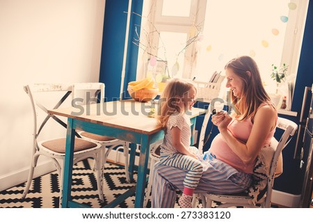 lifestyle capture of pregnant woman with daughter playing on the kitchen with modern interior - stock photo