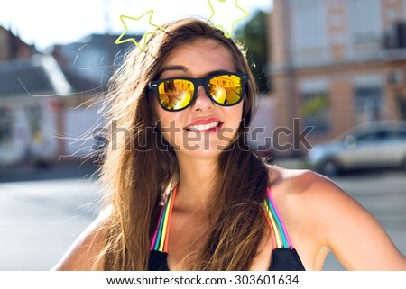 Lifestyle close up portrait of smiling pretty tanned woman, wearing mirrored sunglasses and funny party hair accessory, sunny colors, perfect skin, long brunette hairs, posing on the street. - stock photo