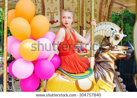 Lifestyle concept, attractive teenager with colorful latex balloons in the amusement park riding a carousel - stock photo