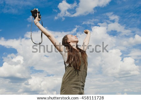 Lifestyle concept - beautiful happy woman enjoying summer outdoors. Girl with vintage camera.