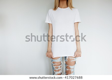 Lifestyle concept. Cropped shot of attractive young female wearing blank copy space T-shirt for your text or promotional content. Hipster blond model with slim body posing isolated indoor - stock photo