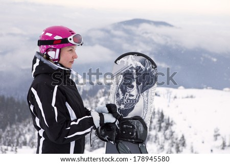 lifestyle concept - woman holding snowboard, she's looking away and smiling, copy space, close-up - stock photo