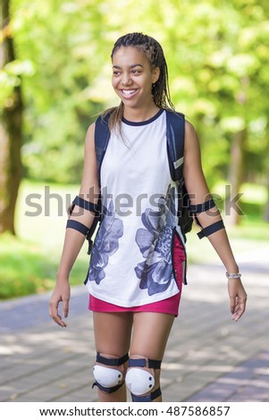 LIfestyle Concepts. African American Teenager Skating on Rollers Outdoors. Vertical Image
