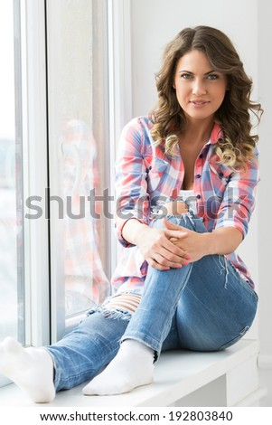 Lifestyle. Cute, attractive woman by the window