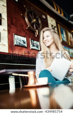 Lifestyle happy young woman in a cafe using a digital tablet and drinking coffee