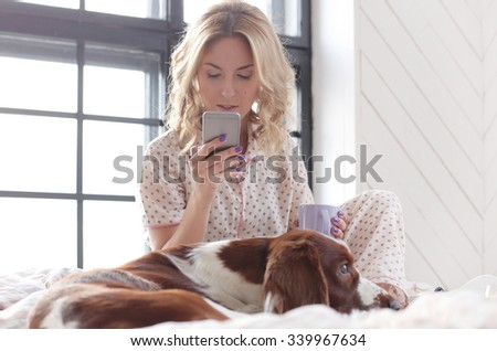 Lifestyle, home. Girl with dog in bed - stock photo