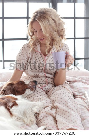 Lifestyle, home. Girl with dog in bed