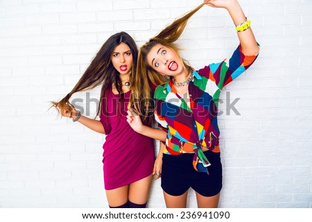 Lifestyle i,age of two young friend girls making crazy funny faces, wearing bright hipster clothes, urban white background. - stock photo