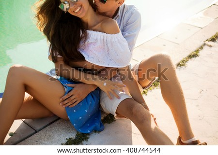Lifestyle image of cheerful young couple in love having fun on lonely beach together . Spring or fall time. Sincerest emotions . Warm sunny colors. - stock photo
