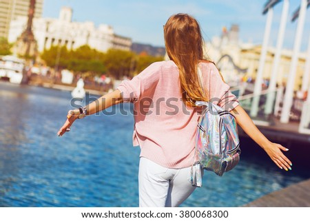 Lifestyle image  of  hipster  girl  in spring casual pastel outfit , trendy jewels, red lips enjoying holidays in Barcelona. - stock photo