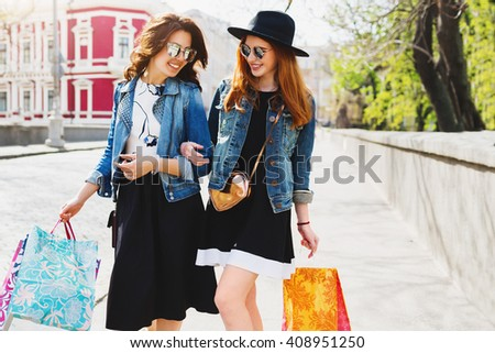 Lifestyle image of two best friends shopping in city center, enjoying vacation, holding paper bags. Couple  of women in trendy fall or spring outfit talking, laughing, enjoying  sunny day. - stock photo