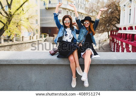 Lifestyle image of  two young pretty friends girls having fun outdoor on the street.  Sitting on the bridge, conversation, laughing, raise  hands up. Positive  mood. Friendship.  - stock photo