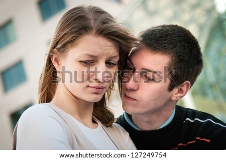 Lifestyle image of young woman and man outside on street having relationship problems - stock photo