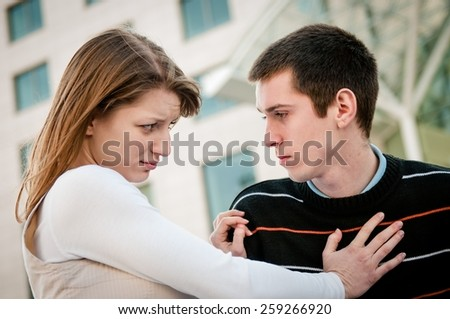 Lifestyle image of young woman refusing man outside on street having relationship problems - stock photo