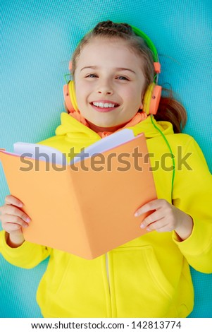 Lifestyle of young people - girl with headphones reading a book - stock photo