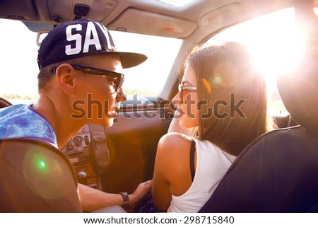 Lifestyle outdoor concept,Young couple looking into each other's eyes.Romantic young couple sitting on hood of their car enjoying the moment,outdoors with copy space.teens in love on a road trip.  - stock photo