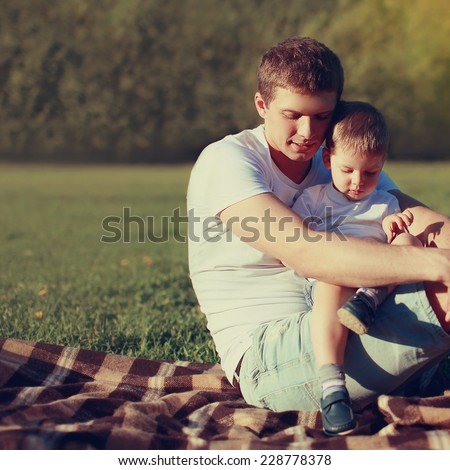 Lifestyle photo lovely father and son together resting outdoors on nature, family values, soft vintage pastel colors - stock photo