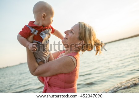 Lifestyle photo normal family with baby boys on the ocean coast - stock photo