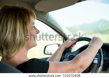Lifestyle photo of attractive senior woman driving car - stock photo