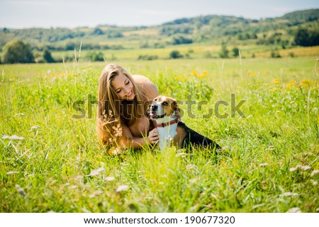 Lifestyle photo of happy young girl with her pet (beagle dog) - outdoor in nature - stock photo