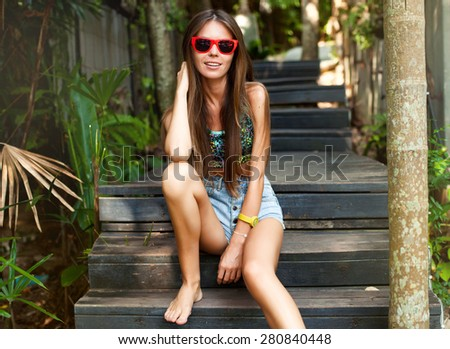 Lifestyle portrait bright toned colors.Vogue style portrait of young fashionable woman in summer sunglasses.Pretty girl posing at tropical alley in soft evening or sunset light,summer mood,stylish - stock photo