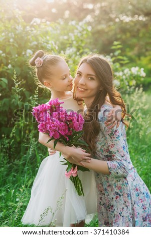 Lifestyle portrait mom and daughter are hugging in happiness in the meadow outdoor in the garden.  Mother and kid with flowers, family relationship on nature. - stock photo