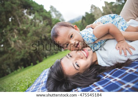 Lifestyle portrait mom and daughter in happiness at the outside in the meadow