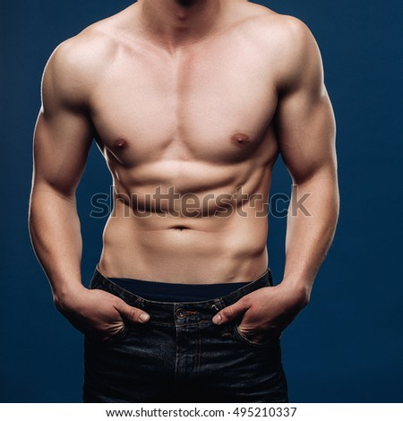 Lifestyle portrait of a male model with a muscular torso looking at the camera, hands in the pocket of the jeans, pants up top. The Blue background of the Studio