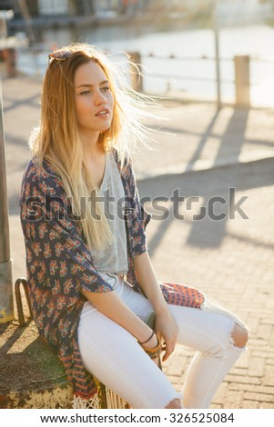Lifestyle portrait of a young attractive woman outdoors - stock photo